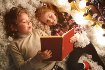 small children-a boy with curly hair and a girl with red hair lie on a soft white carpet near a Christmas tree and read a book of fairy tales on Christmas or New Year's eve.