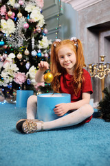 a cute little girl with red hair takes a Christmas tree toy from a box on the background of a Christmas tree and smiles