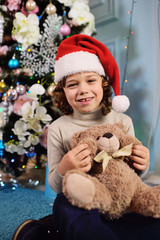 a little baby boy with curly hair in a red Santa hat holding a Teddy bear on the background of a Christmas tree and decor.