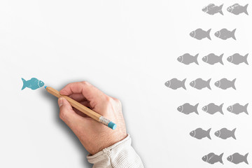 standing out from the crowd or leadership concept with group of fishes going in one direction and one going in opposite direction