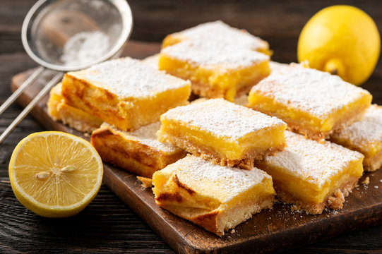 Homemade lemon bars with shortbread crust, on wooden background.