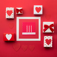Handmade wrapped gift boxes, red hearts and candles, red background