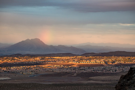 USA, Nevada, Clark County, Henderson. A sunset, sun dog rainbow, and Frenchman Mountain over the Sun City Anthem planned community neighborhood south of Las Vegas.