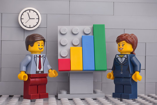Tambov, Russian Federation - November 23, 2019 Two Lego minifigure businessmen having a meeting and discussing graphs showing the results of their successful teamwork.