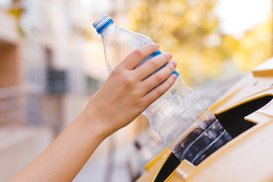 Stock photo of a woman's hand recycling a plastic bottle
