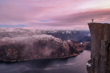 Man hiker standing on the famous Preikestolen over the Lysefjord, beautiful colors at sunset, Ryfylke, Rogaland, Norway