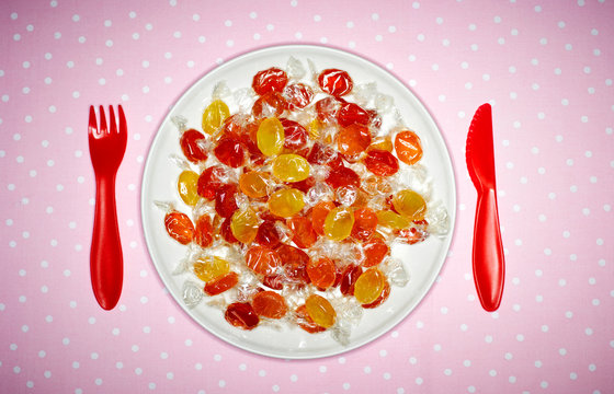 Plate of candies and red plastic cutlery on pink cloth