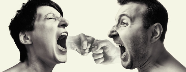 Man and woman yell at each other on light background. Male and female fists on the back burner.