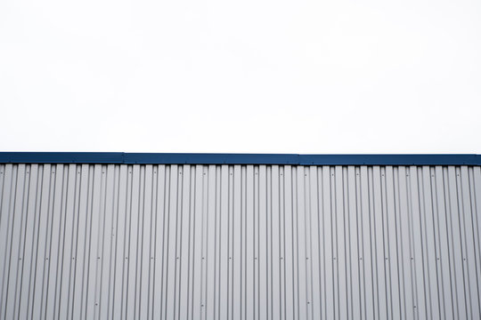 Metal corrugated sheets on a building with a blue metal corners. White aluminium metal corrugated roof or wall sheets against cloudy sky background on a factories and industrial buildings.