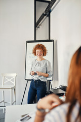 Smiling businesswoman leading a presentation at flip chart in conference room