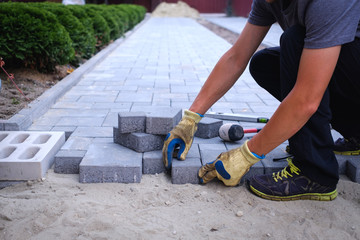 The master in yellow gloves lays paving stones