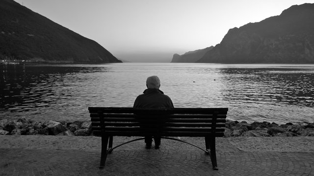 A lonely old man sits on a wooden bench at dusk after sunset, looking at the lake and the light on the horizon.