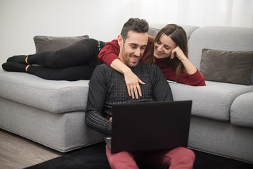 Happy couple using a laptop computer in their house