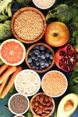 Healthy food clean eating selection: fruit, vegetable, seeds, superfood, cereals, leaf vegetable on rustic background