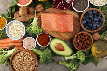 Healthy food clean eating selection: fish, fruit, vegetable, cereal, leaf vegetable on rustic...