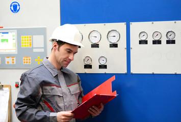 Industriearbeiter kontrolliert Anlage in einer modernen Fabrik // Industrial worker controls plant in a modern factory