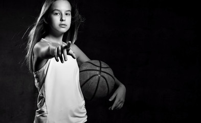 Beautiful caucasian teen woman in sportswear playing basketball . Sport concept isolated on black background.