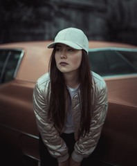 Woman in baseball cap and shiny jacket standing in front of vintage car