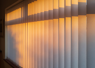 White textured vertical slat blinds hanging in front of a window as the sun is setting turning the light golden. Wall mural