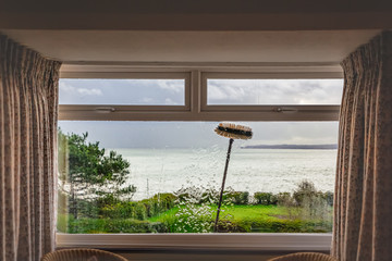 A double glazed picture window with small top light opening windows being cleaned with an extension brush and pure water. Some motion blur showing the movement of the brush. There is a sea view.