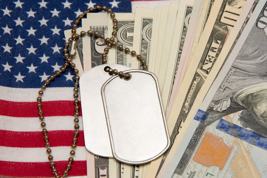 Against the background of the American flag and dollar bills lie army identification medallions. Concept: military pension, salary in the army, insurance for the military, mercenaries and contractors.