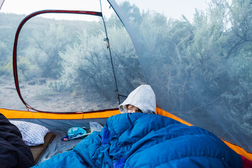 Boy waking up in tent