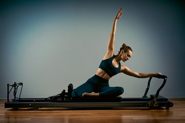 Young girl doing pilates exercises with a reformer bed. Beautiful slim fitness trainer on reformer...