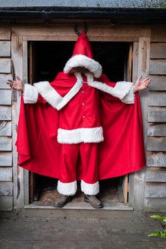 Man wearing Santa Claus costume standing in a workshop doorway.