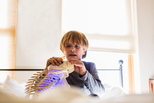 Boy playing with toy on bed at home