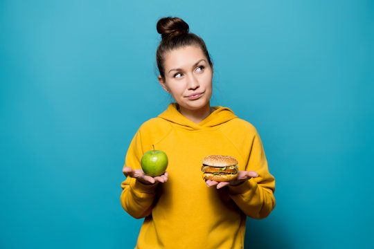 nice girl thinks about the choice between an apple and a burger, which she holds in her hands
