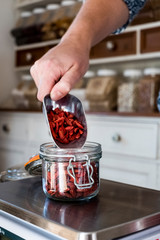 Close up of person weighing Goji berries in glass jar on kitchen scales.