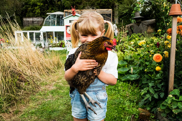 Portrait of girl holding chicken in garden