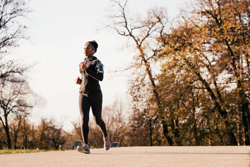 Black athletic woman jogging in autumn day at the park.