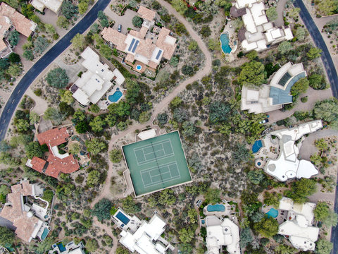 Aerial top view of upscale luxury homes with pool and tennis court in Scottsdale, Phoenix, Arizona