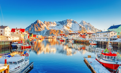 Beautiful Winter nature scene of fishing town on Lofoten Islands in Norway. Amazing sunny landscape of traditional houses rorbu and fishing boats in harbor.