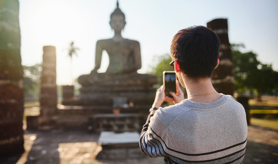young thai male tourist taking photo with smartphone at sukhothai historical park thailand
