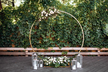 Wedding ceremony. Beautiful wedding round arch decorated with flowers, greenery and candles, outdoors Fotomurales