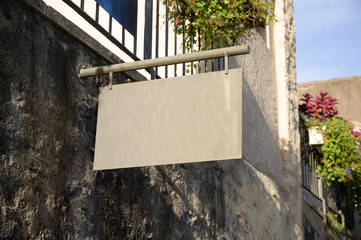 A blank metal sign hinging from a stone wall with space for text.