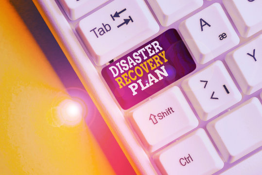 Writing note showing Disaster Recovery Plan. Business concept for having backup measures against dangerous situation White pc keyboard with note paper above the white background