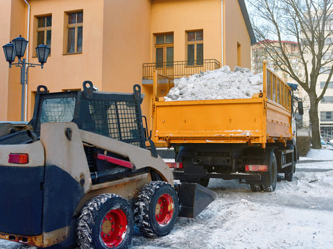Small loader removing and loading snow into a truck. Skid steer loading snow on dump truck. Cleaning city street after blizzard or snowfall. Wheel loader clearing and removing snow in winter
