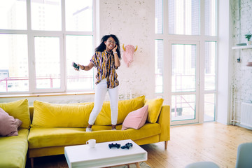 Joyful African American woman standing on couch and listening to music