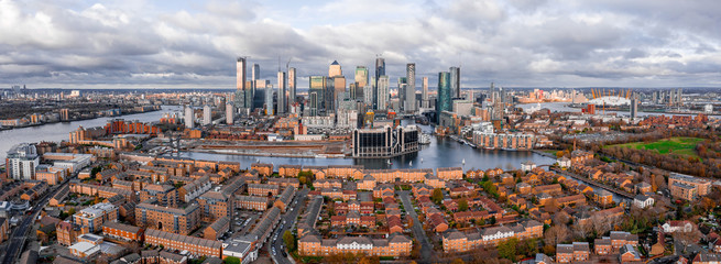 Wall Mural - London, England - Aerial Panoramic skyline view of Bank and Canary Wharf, central London's leading financial districts with famous skyscrapers at golden hour sunset during cloudy skies.