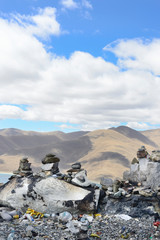 Cairns mark a mountaintop overlooking Lake Yamdrok of the Tibetan Plateau in Brahmaputra Valley of the Tibet Autonomous Region of China.