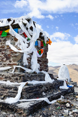 White silk scarves and prayer flags drape a stone column located in Gampa Pass in the Brahmaputra Valley of Tibetan Plateau in Tibet Autonomous Region, China.
