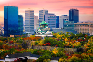 Foto auf Leinwand Rosa hell Osaka castle at the season change of autumn with the modern city urban building present in background at sunrise scenery