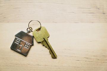One golden house key with house shape keychain isolated on wood background