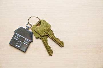 Two golden house keys with house shape keychain isolated on wood background