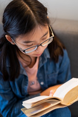 Asian teenage girl reading book and sitting on couch at home