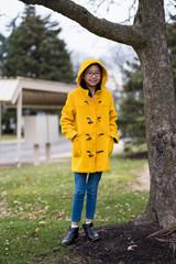 Beautiful asian teen girl in yellow coat outside during autumn