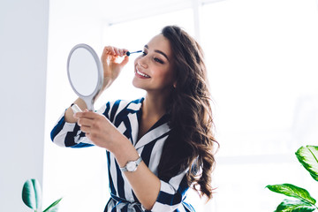 Young happy female looking at mirror and putting mascara